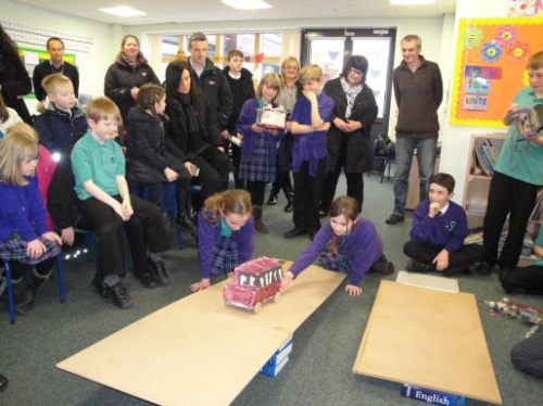 Two Kinnaird Primary School Technology Club members demonstrate their battery powered car on a ramp, with Mark Williams looking on